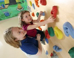 Girl receiving assistance on the climbing wall