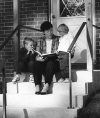 Woman on steps reading to children