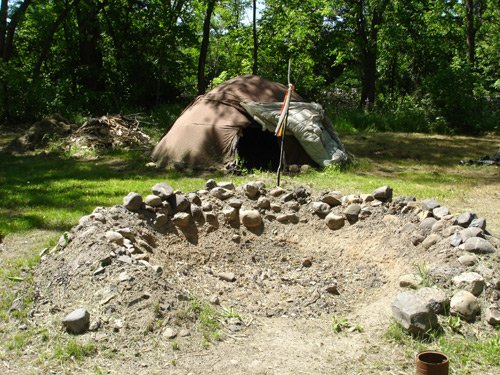 Sweat lodge and fire pit for heating stones used in the purification ceremony