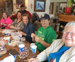 Kay Sime and faith community friends making prayer bead necklaces using Pass it on Crosses.